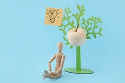 Wooden mannequin and plastic  tree with apple on color background