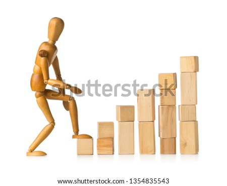 Wooden mannequin figure taking the first step on wooden block building pieces forming steps - career, growth or development concept over white background #1354835543