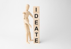 Wooden mannequin near tower of cubes with word ideate on table against light background