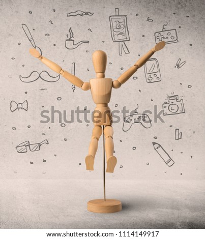 Wooden mannequin posed in front of a greyish background with hobby related scribbles behind it #1114149917
