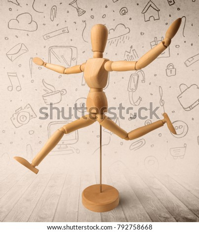 Wooden mannequin posed in front of a greyish background with mixed media scribbles behind it #792758668