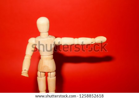 Wooden mannequin posed in front of a red background.A dummy showing something        #1258852618