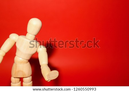 Wooden mannequin posed in front of a red background.Looking at the camera.                                 #1260550993
