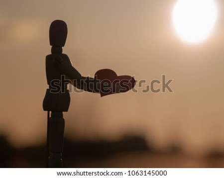 Wooden mannequin with a red heart on his hands Concept of romanticism and love #1063145000