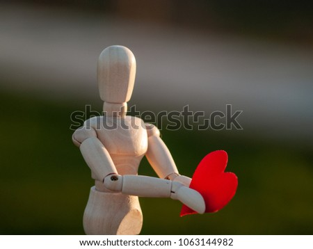Wooden mannequin with a red heart on his hands romanticism and love #1063144982