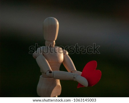 Wooden mannequin with a red heart on his hands romanticism and love #1063145003