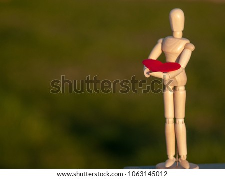 Wooden mannequin with a red heart on his hands romanticism and love #1063145012