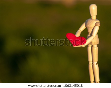 Wooden mannequin with a red heart on his hands romanticism and love #1063145018