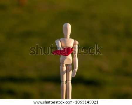 Wooden mannequin with a red heart on his hands romanticism and love #1063145021
