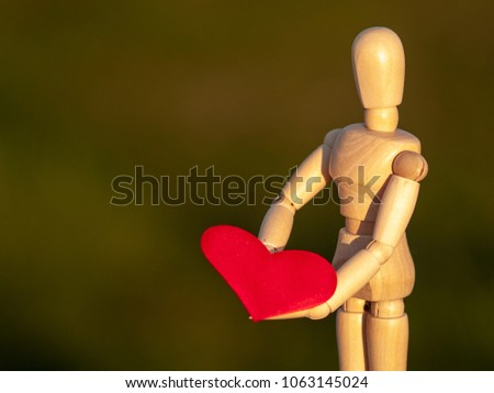 Wooden mannequin with a red heart on his hands romanticism and love #1063145024
