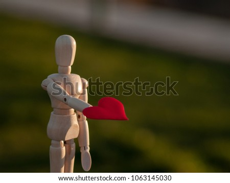 Wooden mannequin with a red heart on his hands romanticism and love #1063145030