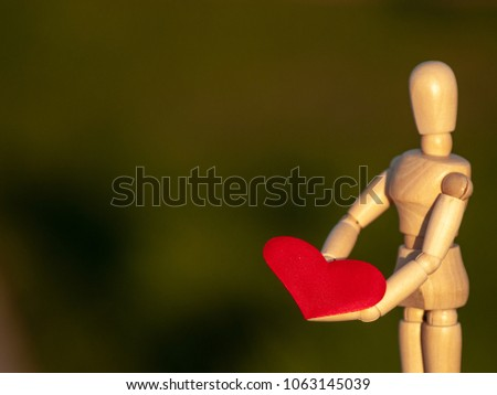 Wooden mannequin with a red heart on his hands romanticism and love #1063145039