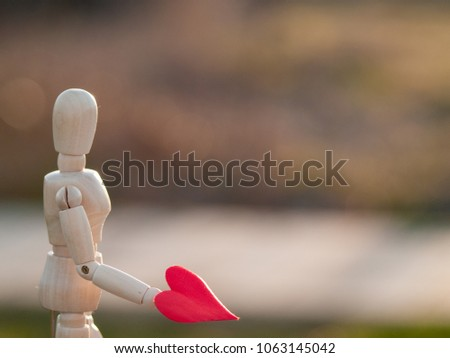 Wooden mannequin with a red heart on his hands romanticism and love #1063145042