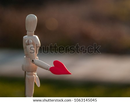Wooden mannequin with a red heart on his hands romanticism and love #1063145045