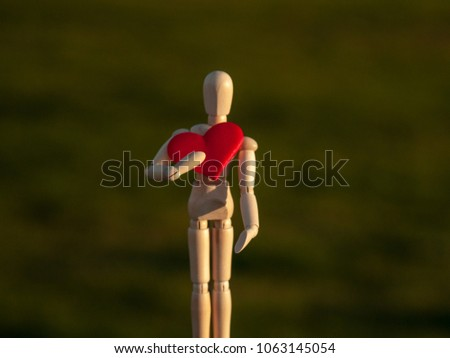 Wooden mannequin with a red heart on his hands romanticism and love #1063145054