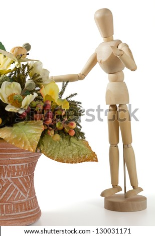 Wooden Mannequin With an Earthenware Jar Full of Flowers