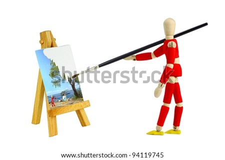 Wooden mannequin with an easel painting a landscape isolated on white