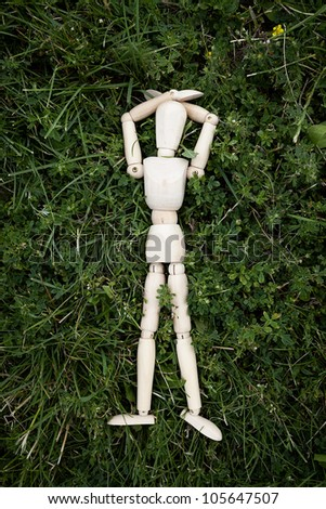 wooden mannequin with arms laid down by the head, lying on green grass