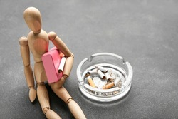 Wooden mannequin with ash tray and cigarettes on dark background
