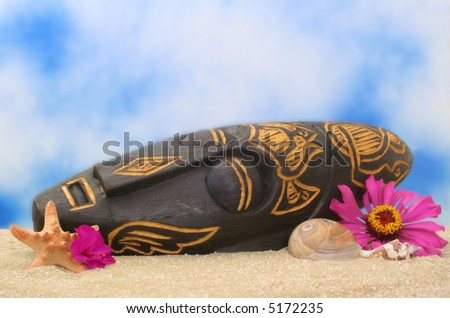 Wooden Mask on Sand With Flowers and Blue Sky Background