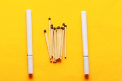 Wooden matches and cigarettes with filter . yellow background