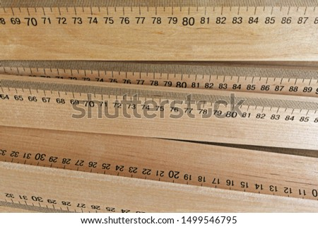 Wooden measuring rulers as a background. Measuring tools represent measurement, metrics, precision, accuracy and results.