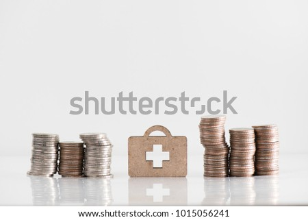 wooden medicine bag model and coin stack illustrate financial saving, health insurance concept #1015056241