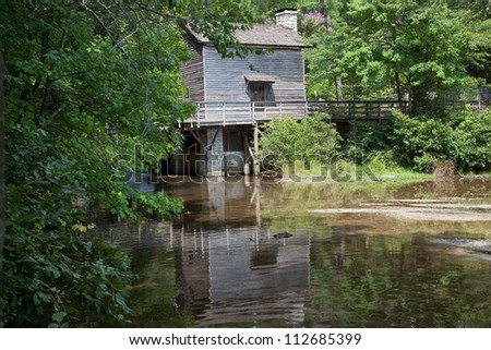 Wooden mill house surrounded by trees and reflected in a lake