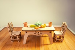 Wooden miniature dollhouse furniture, table and chairs on wooden doll floor. Crafts made of natural wood. Toy dishes,  cabbage, zucchini, carrots, bananas made of polymer clay.