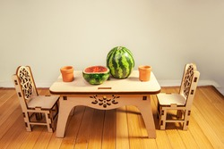 Wooden miniature dollhouse furniture, table and chairs on wooden doll floor. Crafts made of natural wood. Toy dishes,  watermelon cut in the form of and made of polymer clay.