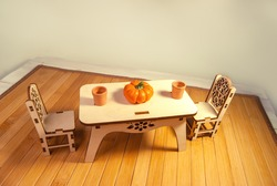 Wooden miniature dollhouse furniture, table and chairs on wooden doll floor. Crafts made of natural wood. Toy dishes, pumpkin made of polymer clay.