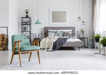 Wooden mint armchair standing on a bright carpet in cozy room with bed #689998021