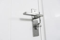Wooden modern door , stainless door knob or handle on wooden door.