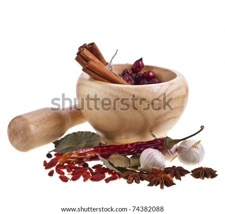 Wooden mortar, dogrose berries and spices isolated on white background