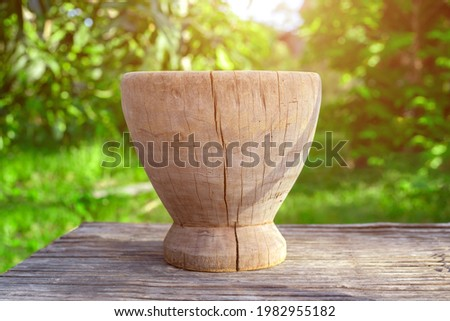Wooden mortar on bamboo table green nature background. Selective focus Foto stock ©
