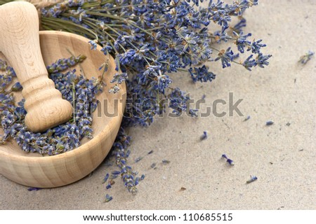 wooden mortar with dry lavender flowers over grungy paper background