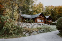 Wooden mountain house built from wood logs. Beautiful log house with porch, patio and driveway in peaceful forest scenery, Canada