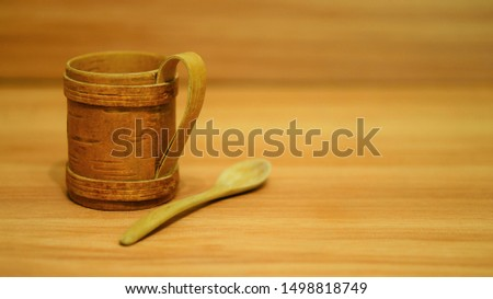 Wooden mug with wooden spoon on wooden table