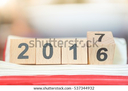 Wooden number block 2016 and 2017 on red book, for conuting End of Year and Happy New year day celebration background concept #537344932