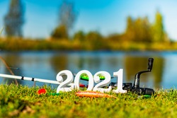 Wooden numbers 2021 on the background of fishing tackle and lures.
