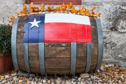 Wooden oak barrel with Texas flag painted on/ Decorative oak barrel in front of Texas winery