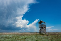 Wooden observation tower in the Tuzly Lagoons National Nature Park. A thunderstorm is approaching in the sky.
