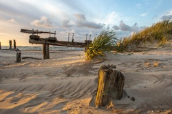 Wooden old bridge ruins , rotten pole construction with rusted metal parts. Baltic Sea coast near Sventoji in Lithuania.