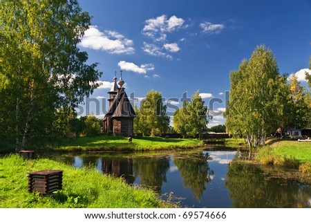 Wooden old church in park. Autumnal landscape