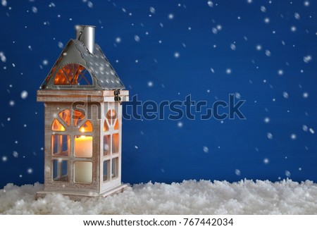 Wooden old house with candle over the snow and blue background - Shutterstock ID 767442034