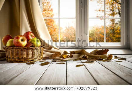 Wooden old table in an autumnal warm day in the sunshine and falling leaves from the trees