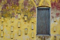Wooden old window with mosquito net frame on a concrete weathered yellow wall as background.