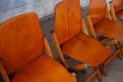 Wooden oldfashion collapsible chairs in a row ready for a conference meeting