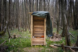 Wooden outhouse compost toilet with toilet seat, toilet paper and door curtain outdoors in the woods.