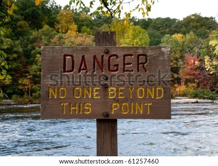 Wooden painted danger sign by rushing river